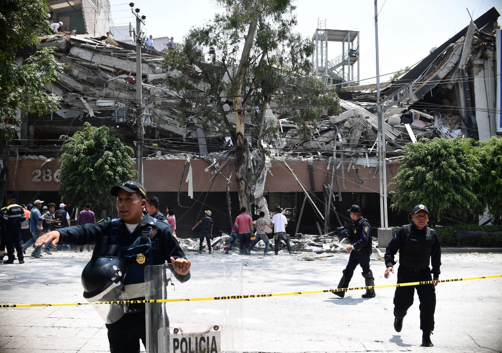 Police officers cordon the area off after a building collapsed during a quake in Mexico City on Sept. 19, 2017. A powerful earthquake shook Mexico City on Tuesday, causing panic among the megalopolis' 20 million inhabitants on the 32nd anniversary of a devastating 1985 quake. (Ronaldo Schemidt/AFP/Getty Images)