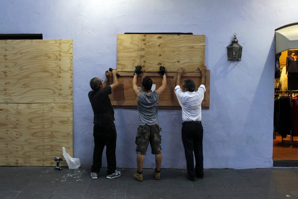 People board up windows of a business in preparation for the anticipated arrival of Hurricane Maria in San Juan, Puerto Rico on Sept. 18, 2017. Hurricane Maria has grown into a maximum-strength Category 5 storm, US forecasters said Monday, as it was bearing down on the Caribbean island of Dominica. (Ricardo Arduengo/AFP/Getty Images)