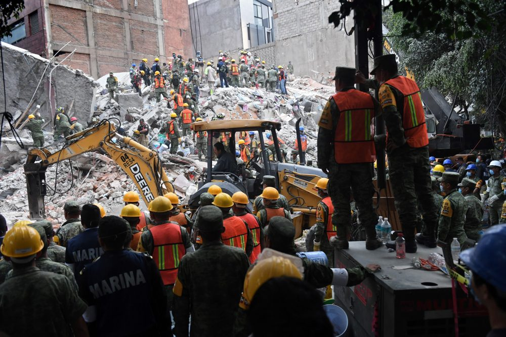 Volunteers remove rubble during the search for survivors in a flattened building in Mexico City on Sept. 20, 2017, after a strong quake hit central Mexico. (Pedro Pardo/AFP/Getty Images)