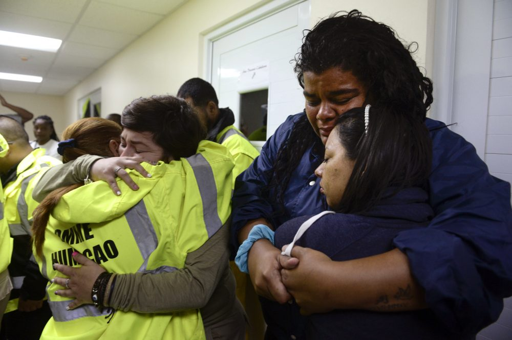 Rescue team members Candida Lozada, left, and Stephanie Rivera, second from left, Mary Rodriguez, second from right, and Zuly Ruiz, right, embrace as they wait to assist in the aftermath of the hurricane in Humacao, Puerto Rico on Wednesday. (Carlos Giusti/AP)