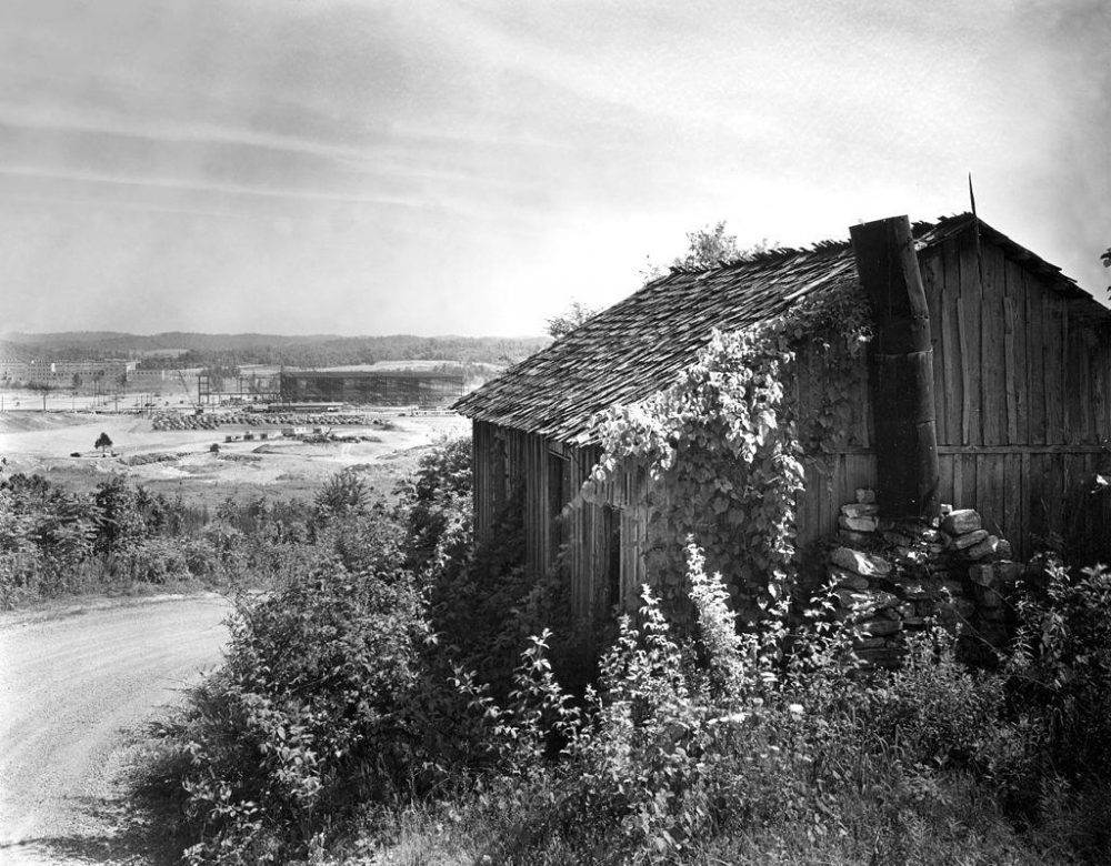 In 1942, original houses in the Oak Ridge area started to be replaced by construction for the war effort. In the background of this photo, K-25 is being built — which used the gaseous diffusion method to enrich uranium. (Ed Wescott/U.S. Department of Energy)