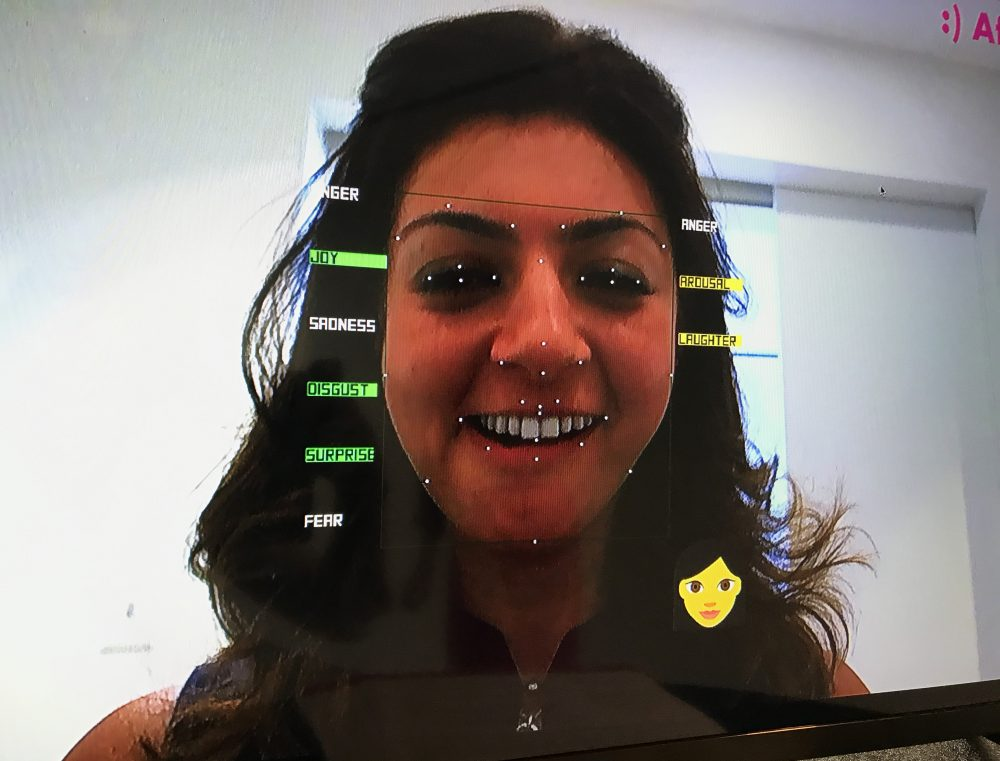 Rana el Kaliouby tests out her company's 'emotion AI' technology. The data points on the left offer analysis of her facial expressions, while the data points on the right refer to her voice and tone. (Asma Khalid/WBUR)