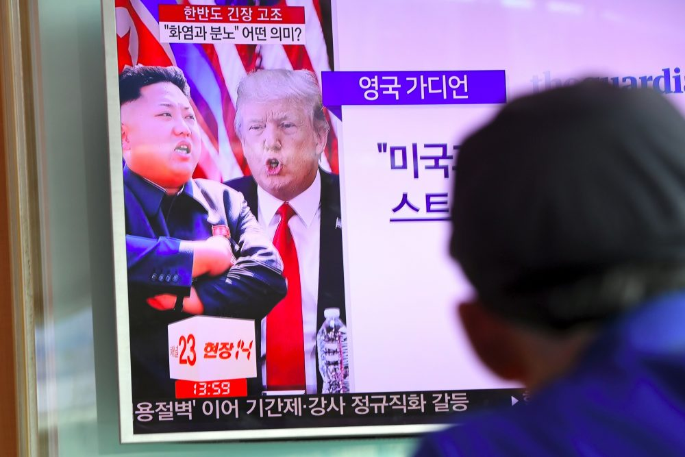 A man watches a television news program showing President Trump and North Korean leader Kim Jong Un at a railway station in Seoul on Aug. 9, 2017. (Jung Yeon-Je/AFP/Getty Images)