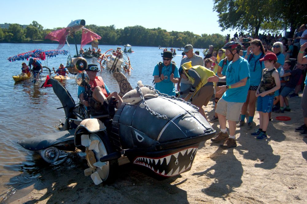 "Jay Hungate's shark-shaped ""Iconic Flying Fish"" rolls out of the Merrimack River. (Greg Cook/WBUR)"