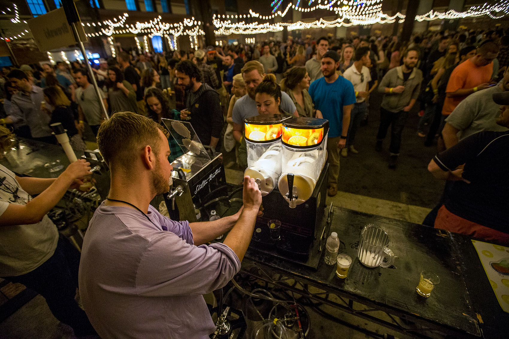 Hundreds gathered for the Copenhagen Beer Festival at the SoWa Power Station in the South End Friday and Saturday. Here, William Blennow of Sweden's Omnipollo Brewing tops a beer with frozen lemonade IPA as he serves a line that stretches to the other end of the building. (Jesse Costa/WBUR)
