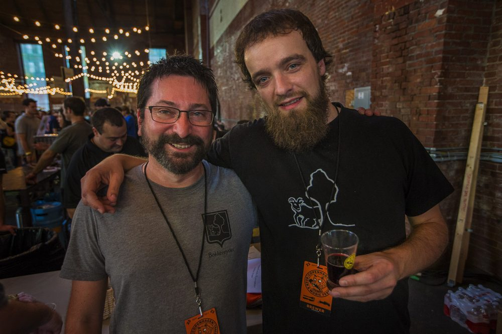 Raf Souvereyns (right) of Bokkereyder holds a glass of his Pinot Kriek, standing with his friend, brewer Eric F. Walker. (Jesse Costa/WBUR)