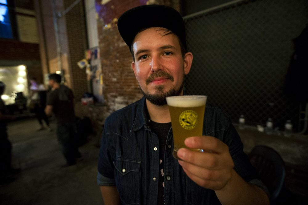Andreas Skytt Larsen, of Alefarm Brewing, holds a glass of his Mimesis Saison. (Jesse Costa/WBUR)