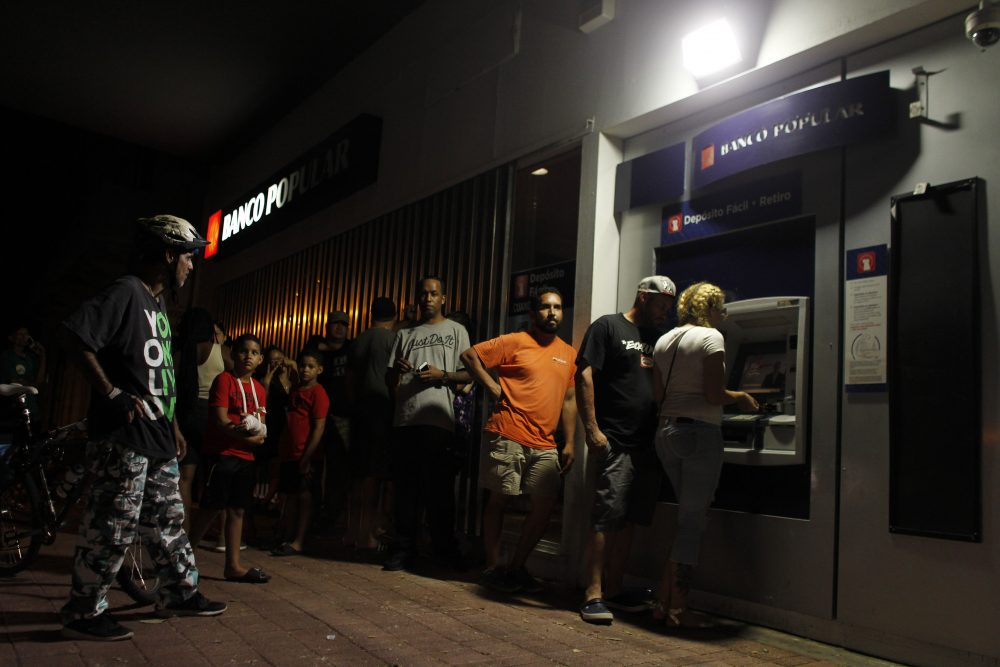 People wait in line at an ATM to withdraw money in San Juan, Puerto Rico, on Sept. 25, 2017, where a 7 p.m. to 6 a.m. curfew has been imposed following Hurricane Maria's impact on the island. (Ricardo Arduengo/AFP/Getty Images)