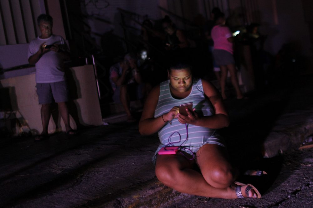 A woman checks her cellphone next to a road at night in one of the few places with cell signal access in San Juan, Puerto Rico, on Sept. 25, 2017. (Ricardo Arduengo/AFP/Getty Images)