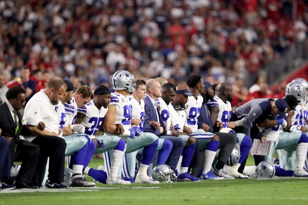Members of the Dallas Cowboys link arms and kneel during the national anthem last Monday night. (Christian Petersen/Getty Images)