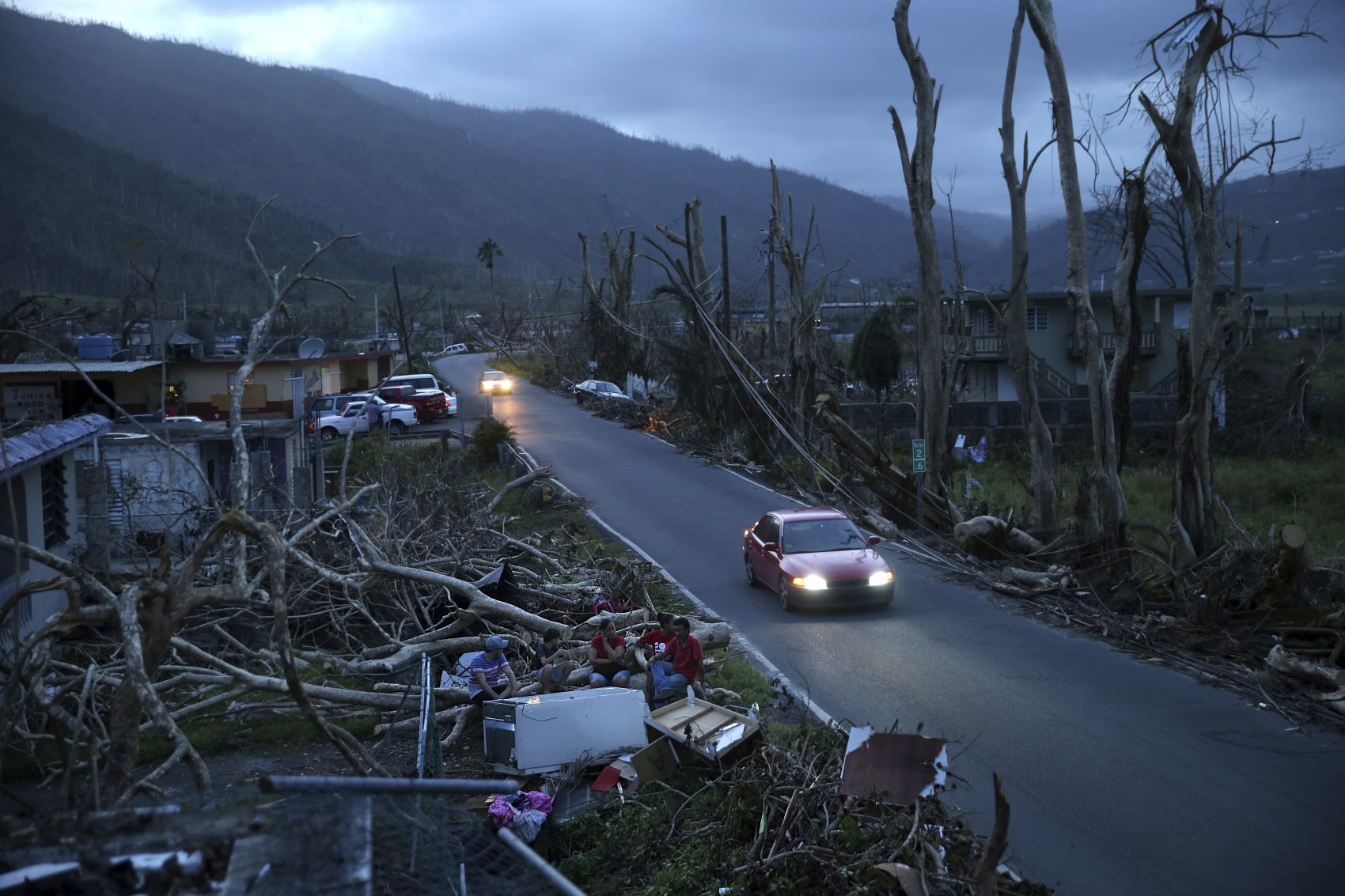Neighbors sit on a couch outside their destroyed homes as sun sets in the aftermath of Hurricane Maria, in Yabucoa, Puerto Rico on Tuesday, Sept. 26. (Gerald Herbert/AP)
