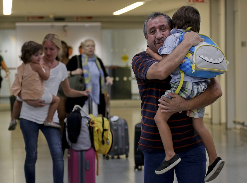 Juan Rojas, right, of Queens, hugs his 4-year-old grandson Elias Rojas, as his daughter-in-law Cori Rojas, left, carries her daughter Lilly, 3, through the terminal at JFK airport after Cori arrived on a flight from San Juan, Puerto Rico, Tuesday, Sept. 26, 2017, in New York. (Julie Jacobson/AP)