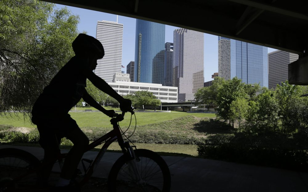 A young boy rides his bicycle along Houston's Buffalo Bayou as it snakes its way into downtown below a highway overpass, Friday, April 18, 2014. (Pat Sullivan/AP)
