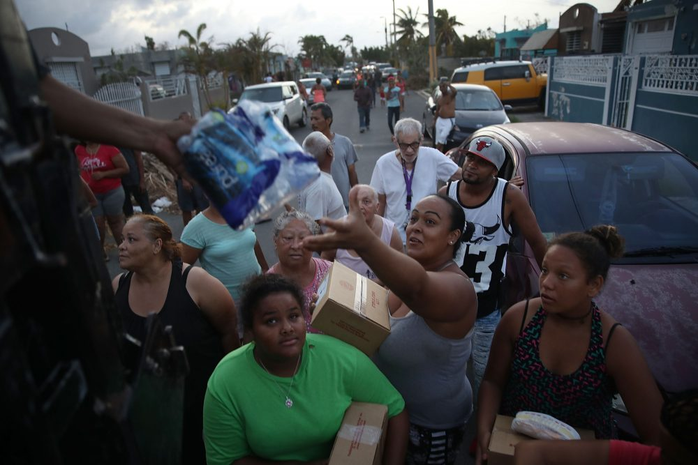 Hurricane survivors receive food and water being given out by volunteers and municipal police as they deal with the aftermath of Hurricane Maria on Sept. 28, 2017, in Toa Baja, Puerto Rico. (Joe Raedle/Getty Images)