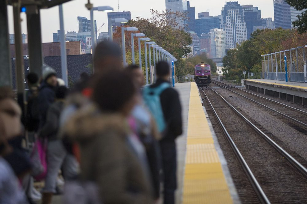 A large group of students on their way to Jeremiah Burke High School wait as the Fairmount Line Commuter Rail train pulls into Uphams Corner Station in early morning. (Jesse Costa/WBUR)