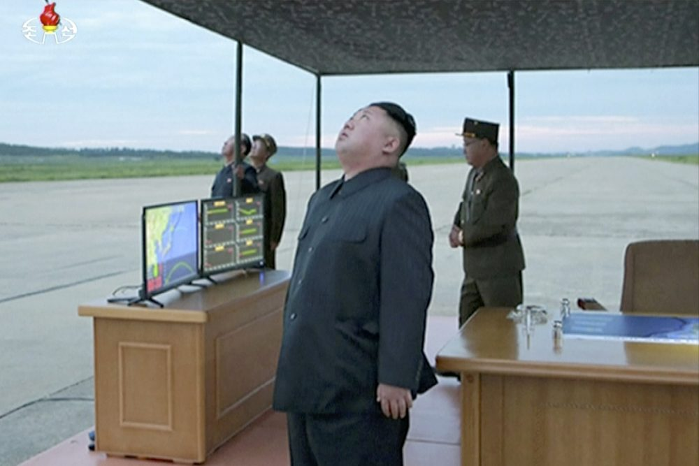 In this image made from video of a news bulletin aired by North Korean government broadcaster KRT on Wednesday, Aug. 30, 2017, leader Kim Jong Un looks up at the sky at what is said to have been a missile launch on Aug. 29, 2017, at an undisclosed location in North Korea.  (KRT via AP Video)