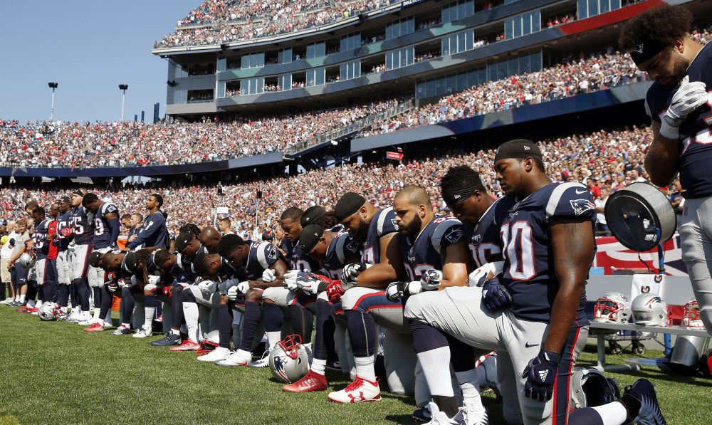 Patriots players kneel during the national anthem before Sunday's game. (Michael Dwyer/AP)