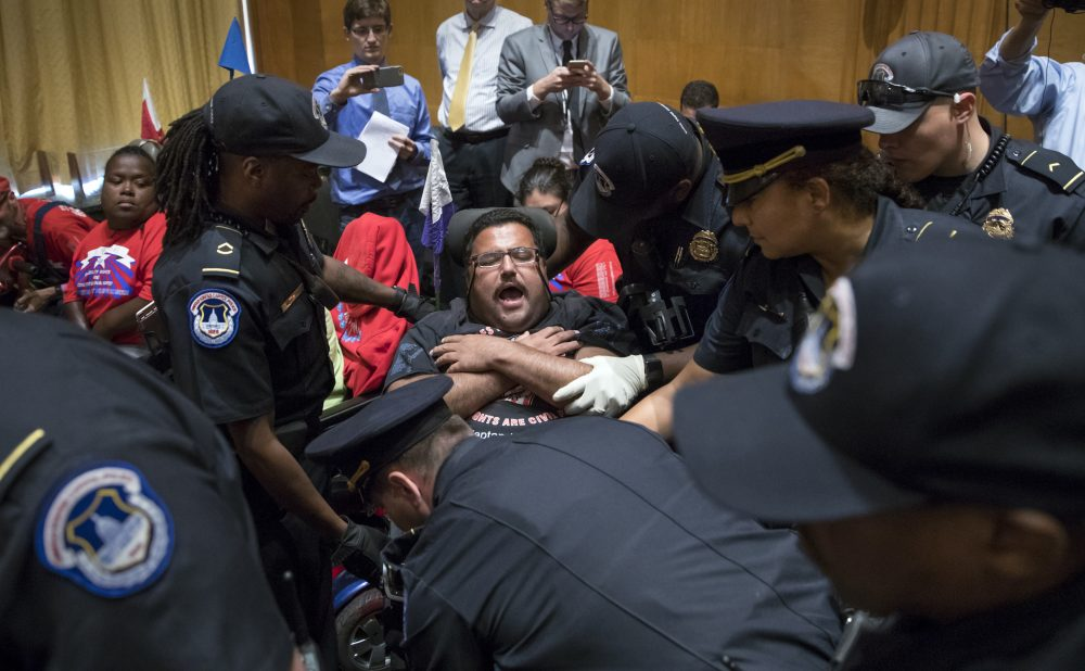 Activists opposed to the GOP's Graham-Cassidy health care repeal bill, many with disabilities, are removed by U.S. Capitol Police after disrupting a Senate Finance Committee hearing on the last-ditch GOP push to overhaul the nation's health care system, on Capitol Hill in Washington, Monday, Sept. 25. (J. Scott Applewhite/AP)