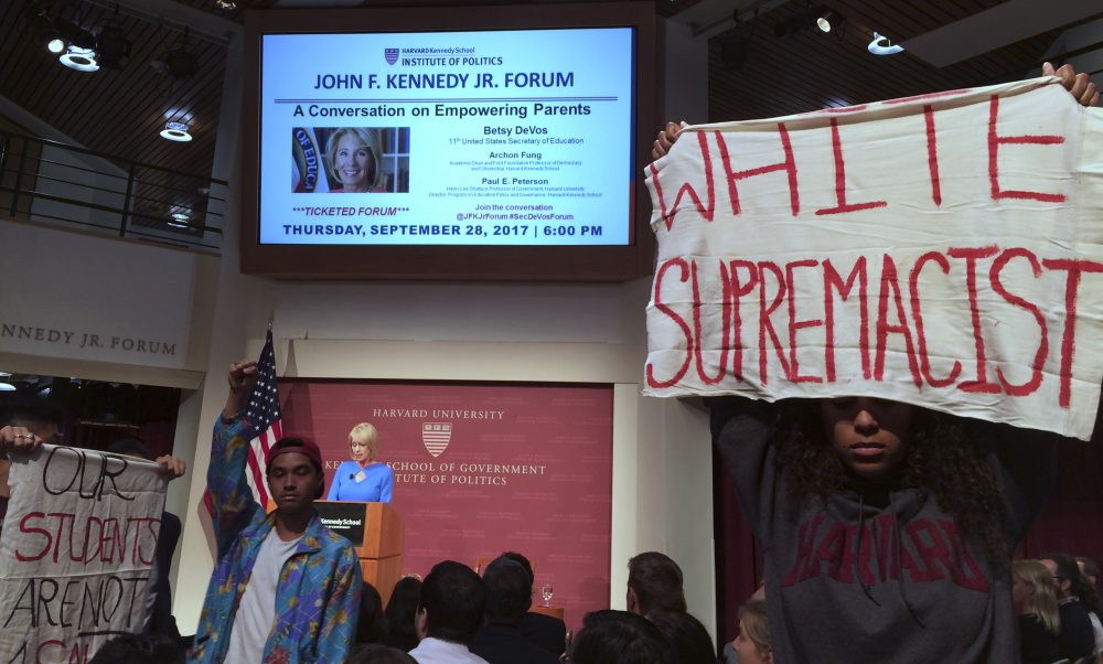 Protesters stand and hold signs and demonstrate during a speech by Education Secretary Betsy DeVos at Harvard University's Kennedy School of Government on Thursday. (Maria Danilova/AP)