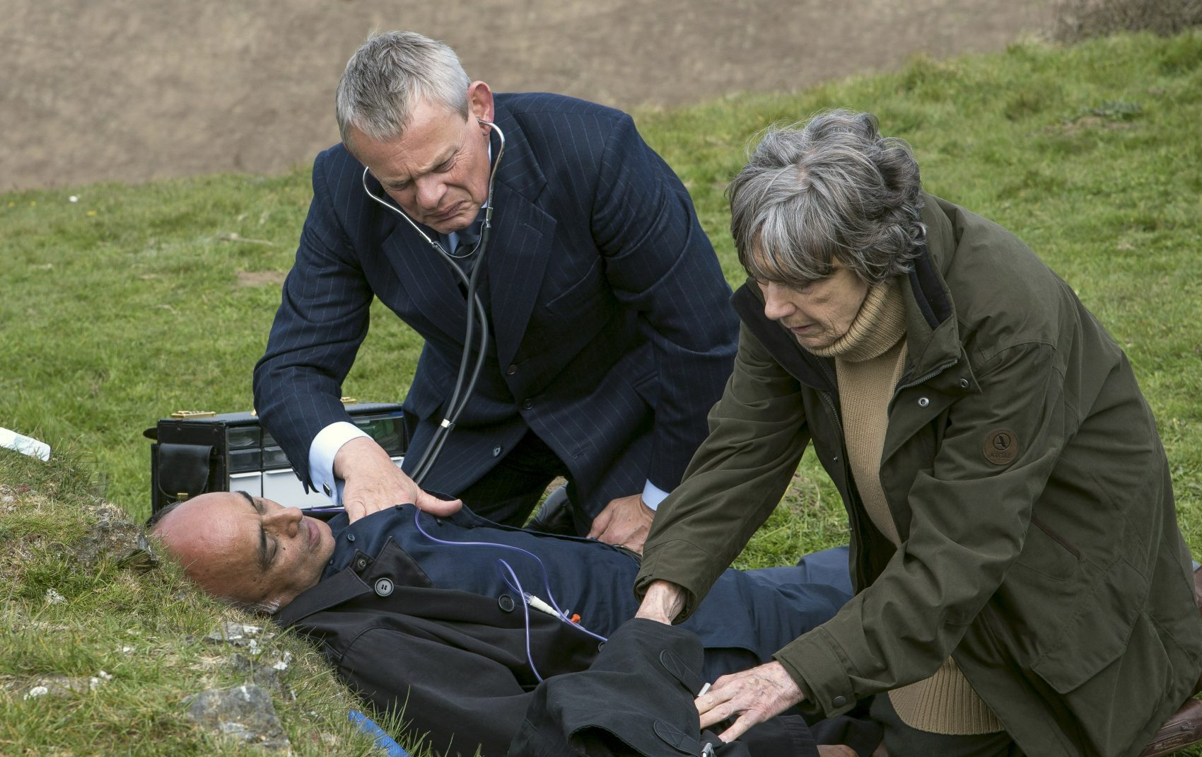 """Martin Clunes as """"Doc Martin"""" tends to Art Malik as a visitor to Portwenn. Eileen Atkins plays his aunt. (Courtesy of Acorn TV)"""