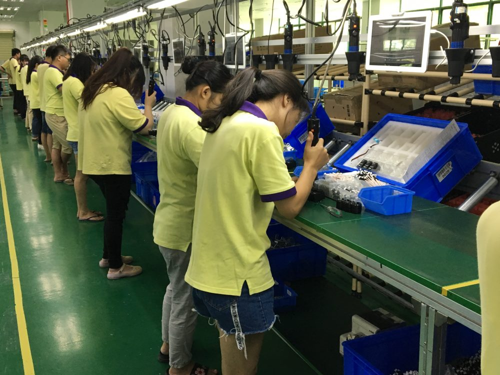 Chinese workers at a robot factory in Shenzhen, China.  (Asma Khalid, WBUR)
