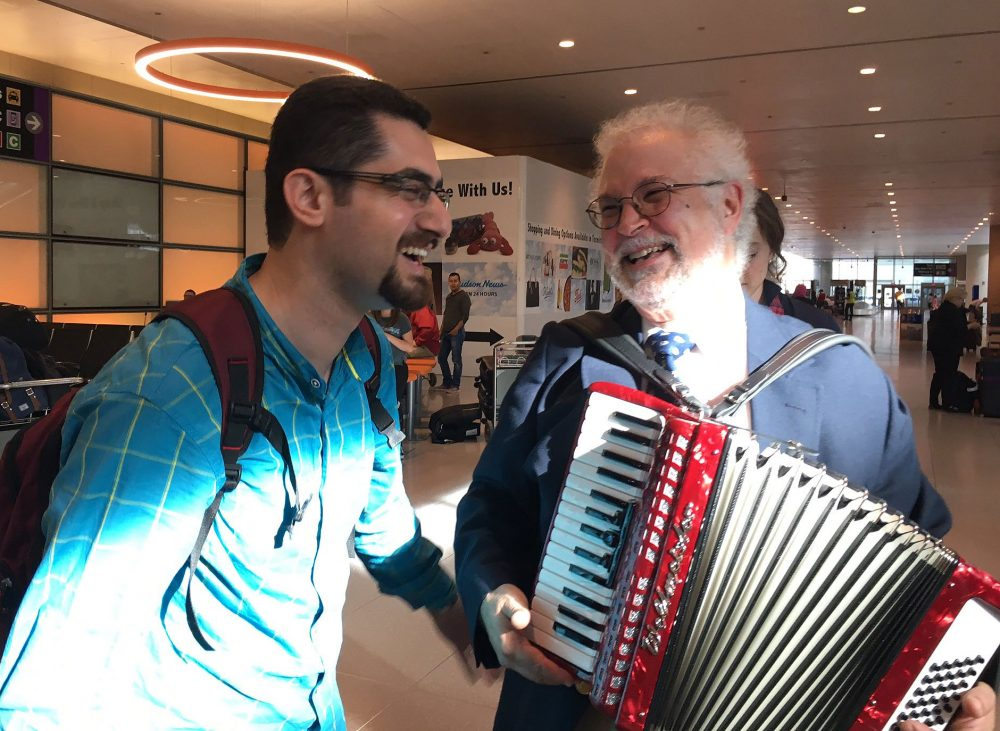 Dr. Seyed Saravi, left, is welcomed to Boston Wednesday by Dr. Thomas Michel and Michel's accordion. (Shannon Dooling/WBUR)