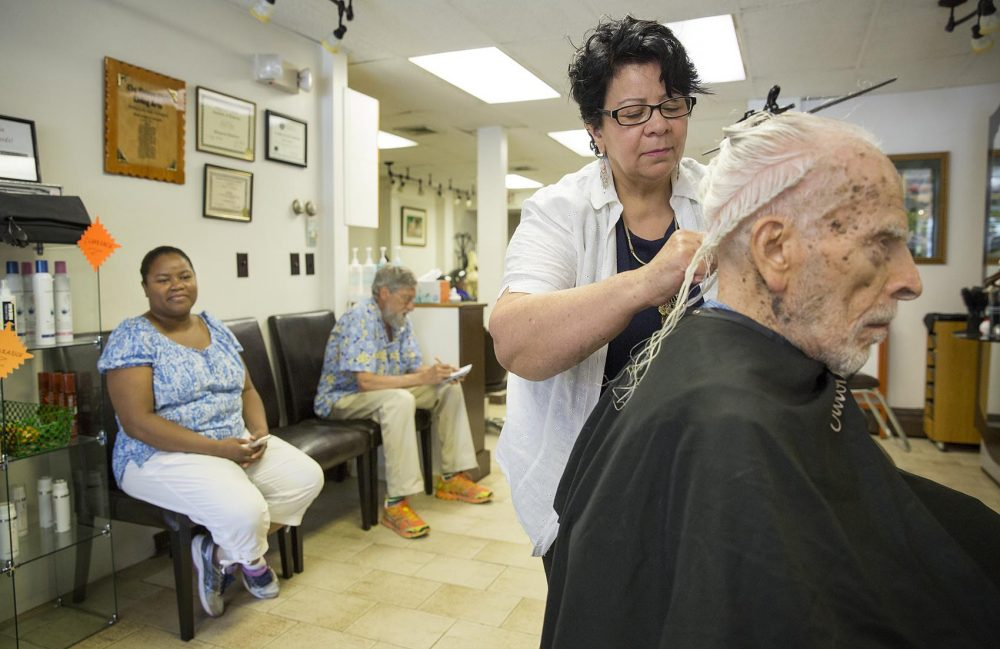 Caretaker Yamiley Jean Louis looks on as Leroy Neuberg, 102, gets his regular haircut from Maria Chavez at Salon Maria in Brookline. (Robin Lubbock/WBUR)