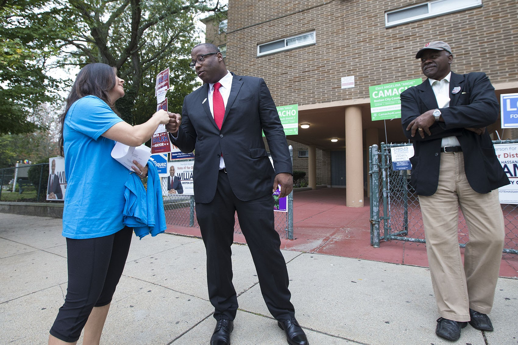 Boston City Councilor Tito Jackson fist bumps with a campaigner outside of the Holgate Apartments in Dorchester shortly after voting on Sept. 26. (Jesse Costa/WBUR)