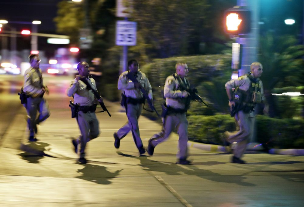 Police run for cover at the scene of a shooting near the Mandalay Bay resort and casino on the Las Vegas Strip on Sunday night. (John Locher/AP)