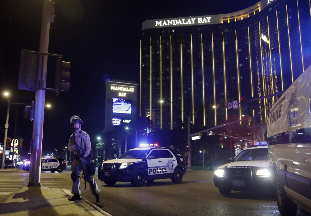 Police officers stand along the Las Vegas Strip on Sunday night. The suspect, Stephen Paddock, 64, a resident of the Las Vegas area, is dead after police confronted him on the 32nd floor of the Mandalay Bay Hotel and Casino. (John Locher/AP)