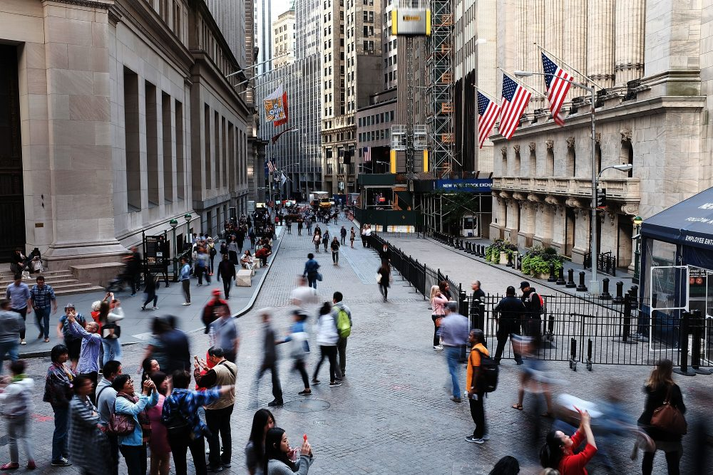 People walk outside of the New York Stock Exchange through Manhattan's financial district on Sept. 29, 2017 in New York City. According to a recent report, America's largest banks could see profits rise by $6.4 billion under Trump's tax plan. (Spencer Platt/Getty Images)
