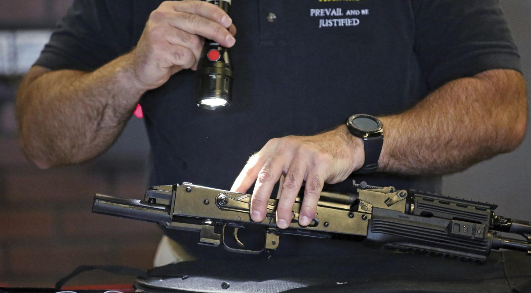 """Clark Aposhian, chairman of the Utah Shooting Sports Council, demonstrates how a little-known device called a """"bump stock"""" works when attached to a semi-automatic rifle at the Gun Vault store and shooting range in Utah. (Rick Bowmer/AP)"""