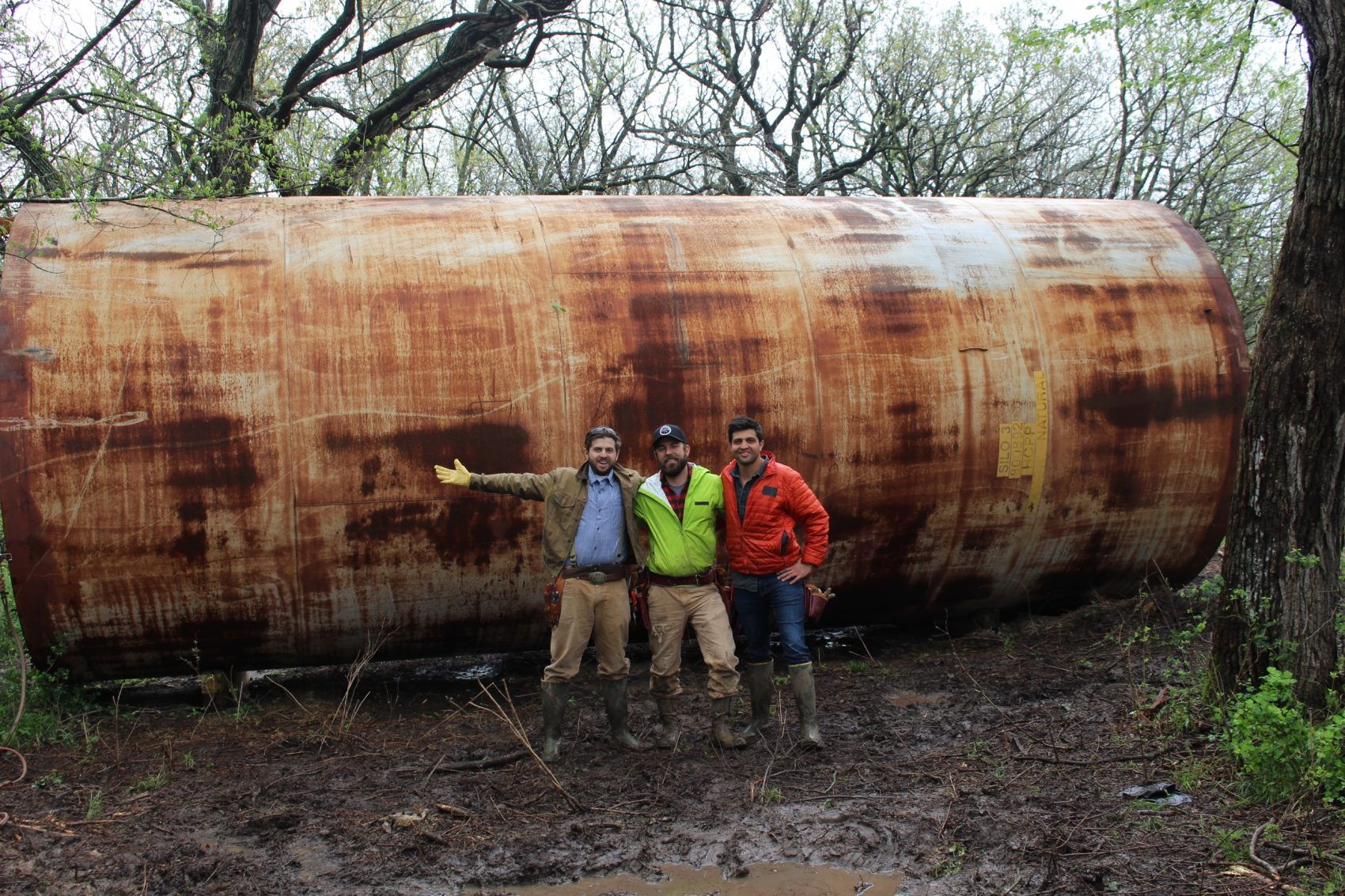 """Rehan Nana (left), Kyle Davis (center) and Taimoor Nana, hosts of """"You Can't Turn That Into A House,"""" in front of an old grain silo. (Courtesy A+E Networks)"""