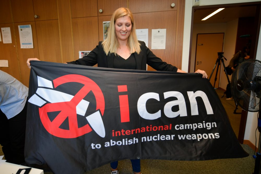 Nuclear disarmament group ICAN executive director Beatrice Fihn holds a banner with their logo after ICAN won the Nobel Peace Prize for its decade-long campaign to rid the world of the atomic bomb as nuclear-fuelled crises swirl over North Korea and Iran, on Oct. 6, 2017, in Geneva. (Fabrice Coffrini/AFP/Getty Images)