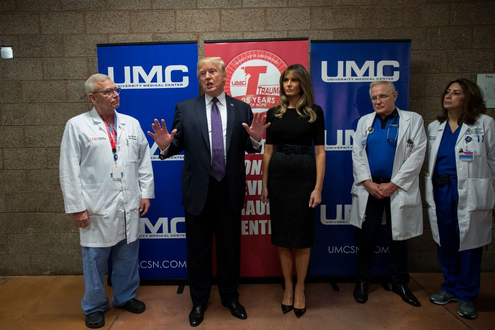Flanked by surgeon Dr. John Fildes (left) and first lady Melania Trump, President Trump speaks to reporters at University Medical Center, Oct. 4, 2017, in Las Vegas. (Drew Angerer/Getty Images)
