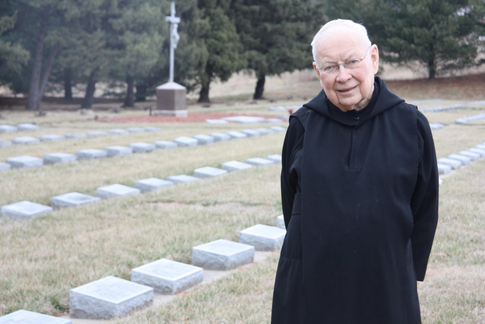 Father Dennis Meade in the abbey cemetery. The Benedictine Monks of Atchison established the monastery in Atchison, Kansas right around the time the state was opening for settlement. (Laura Ziegler/KCUR)