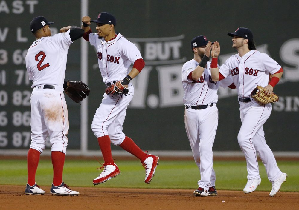 Boston Red Sox's Xander Bogaerts, left, Mookie Betts, second from left, Dustin Pedroia, second from right, and Andrew Benintendi, right, celebrate their 10-3 win over the Houston Astros in Game 3 of baseball's American League Division Series, Sunday, Oct. 8, 2017, in Boston. (Michael Dwyer/AP)