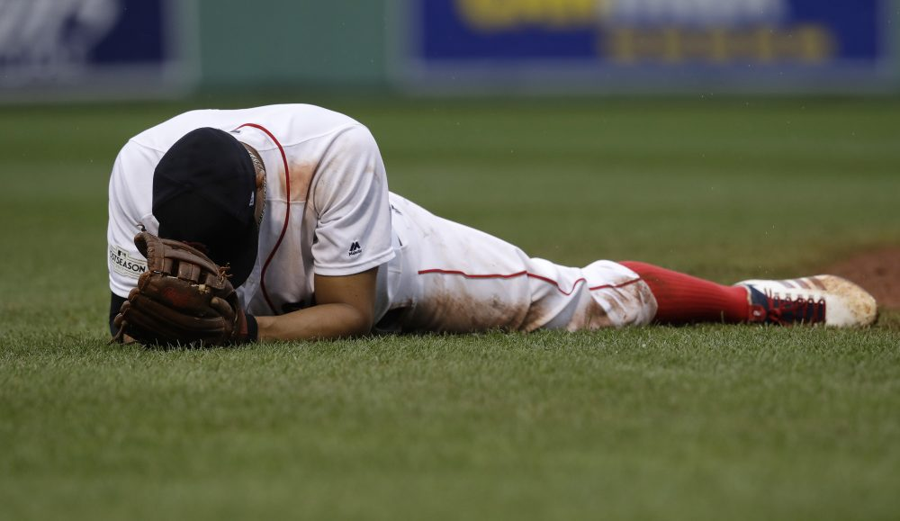 Boston Red Sox shortstop Xander Bogaerts remains on the turf after he was unable to catch up with a ball hit by Josh Reddick, which drove in a run, during the eighth inning in Game 4 of baseball's American League Division Series, Monday, Oct. 9, 2017, in Boston. (AP Photo/Charles Krupa)