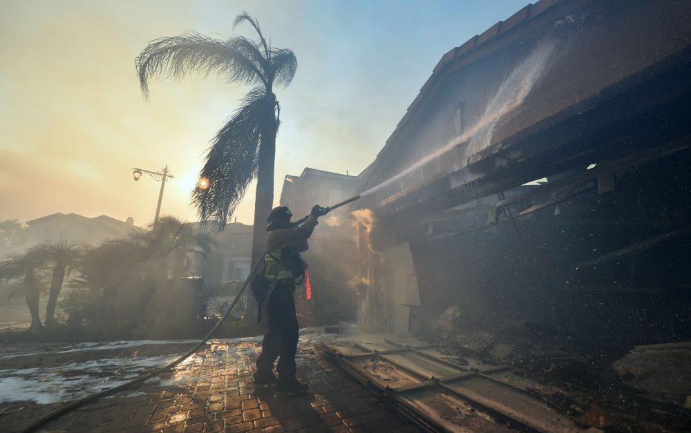 A fireman puts out a fire at a home in the Anaheim Hills neighborhood in Anaheim, Calif., on Oct. 9, 2017, after a fire spread quickly through the area destroying homes, prompting mandatory evacuations and freeway closures. (Frederic J. Brown/AFP/Getty Images)