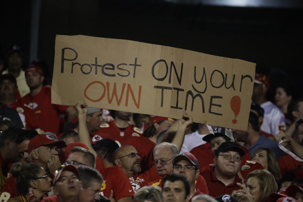 A Kansas City Chiefs fan holds a sign against the anthem protests during the first half of an NFL football game against the Washington Redskins in Kansas City, Mo., Monday, Oct. 2, 2017. (Charlie Riedel/AP)