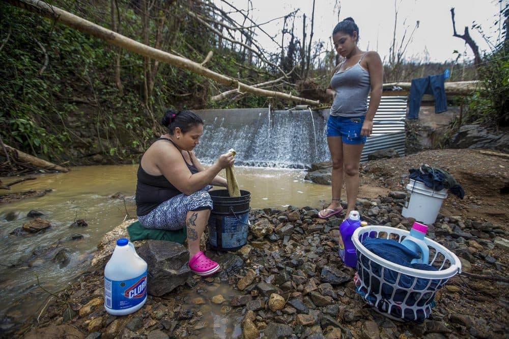 Jacquline Laporte Mammero and her daughter Darielys wash clothes in a stream in  Cuchillas. (Jesse Costa/WBUR)