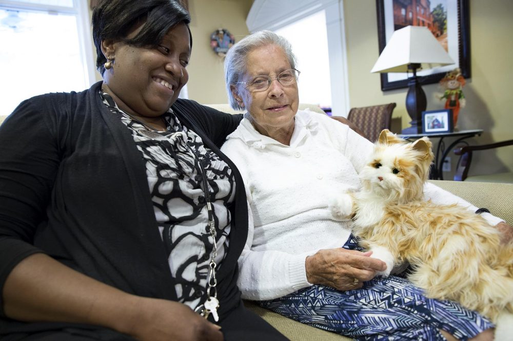 Caretaker Mirlene Desrosiers sits with Lillian Hall and Milo the robotic cat at the Brookdale Senior Living Community in Danvers. (Robin Lubbock/WBUR)