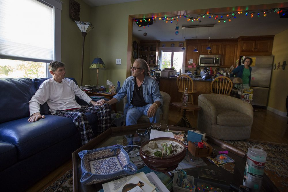 Ron Hoffman, center, and Don Viewegtalk, who has ALS, talk in the living room while Don's wife Dana prepares his lunch. He needs a feeding tube to eat. (Jesse Costa/WBUR)
