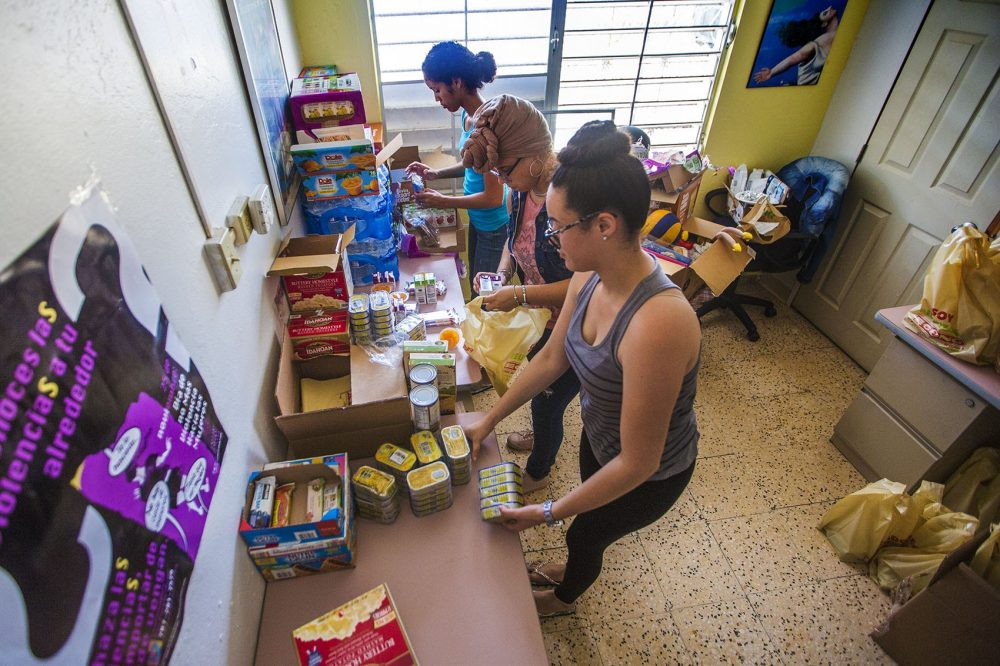 Volunteers of the Taller Salud in Loiza assemble bags of nonperishable food items for residents who need them. (Jesse Costa/WBUR)
