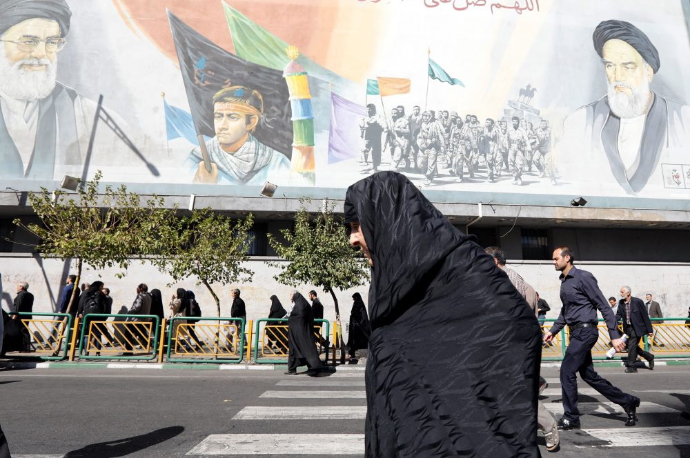 An Iranian woman walks past pictures of Iranian supreme leader Ayatollah Ali Khamenei and of late Iranian supreme leader Ayatollah Ruhollah Khomeini, following the weekly Friday prayer in Tehran on Oct. 13, 2017. (STR/AFP/Getty Images)