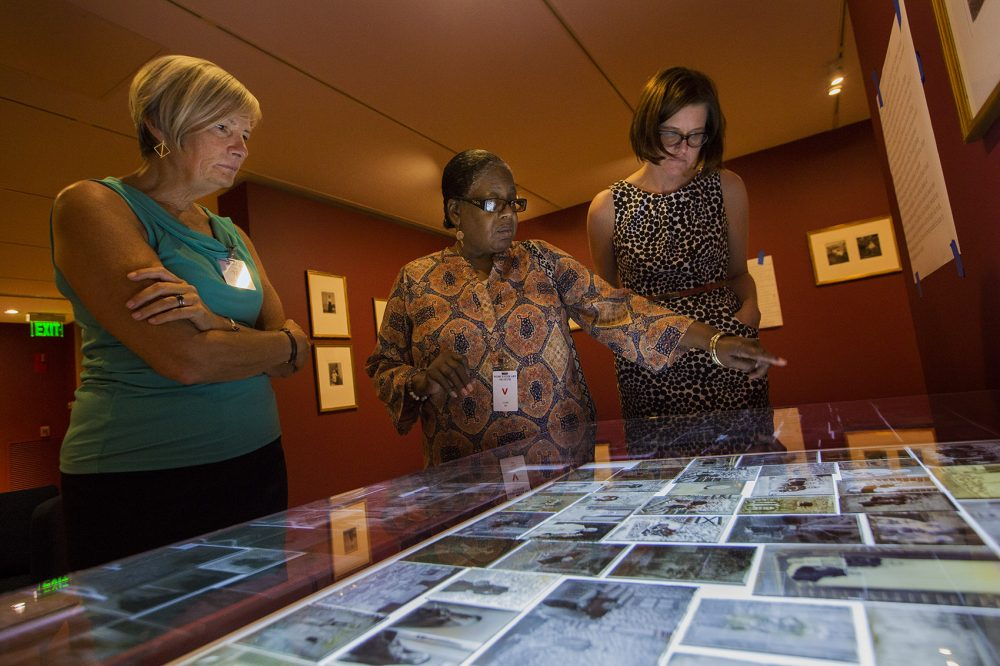 Professor Janette Greenwood, Benetta Kuffour and curator Nancy Burns look at the negatives. (Jesse Costa/WBUR)