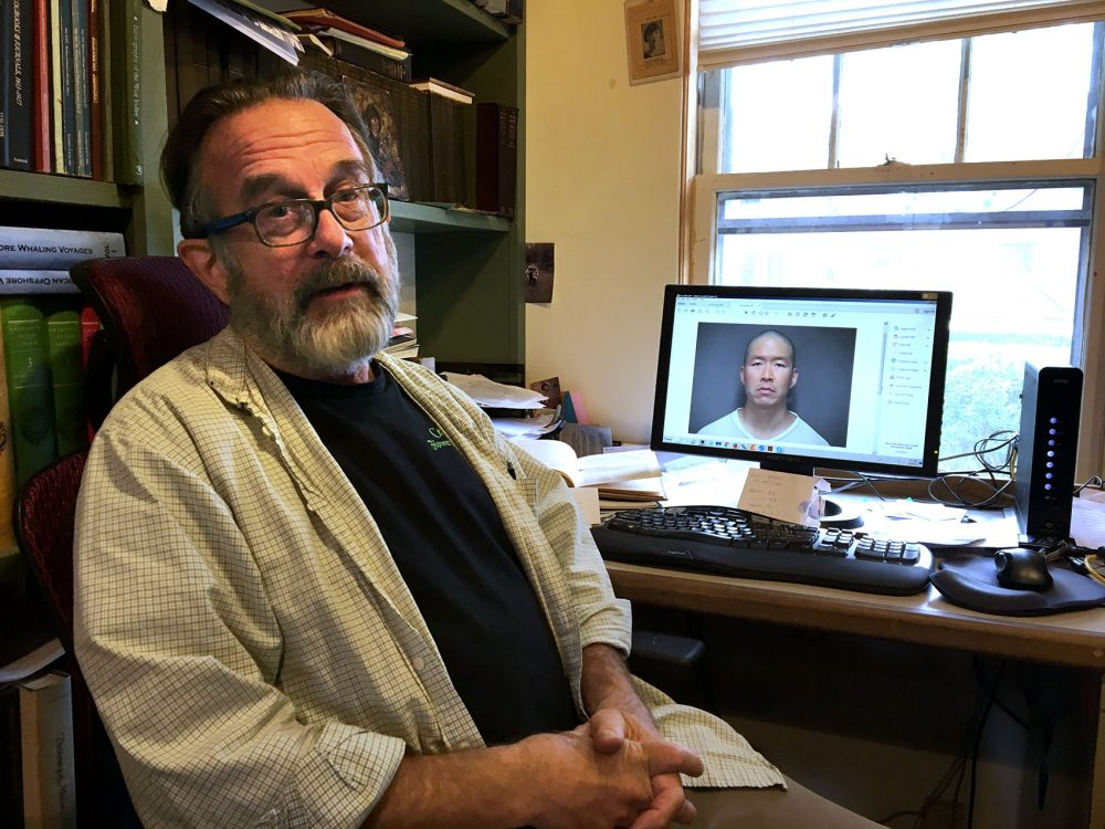 Greg Gibson, with a photo of his son's killer, Wayne Lo, on a computer screen (Anthony Brooks/WBUR)