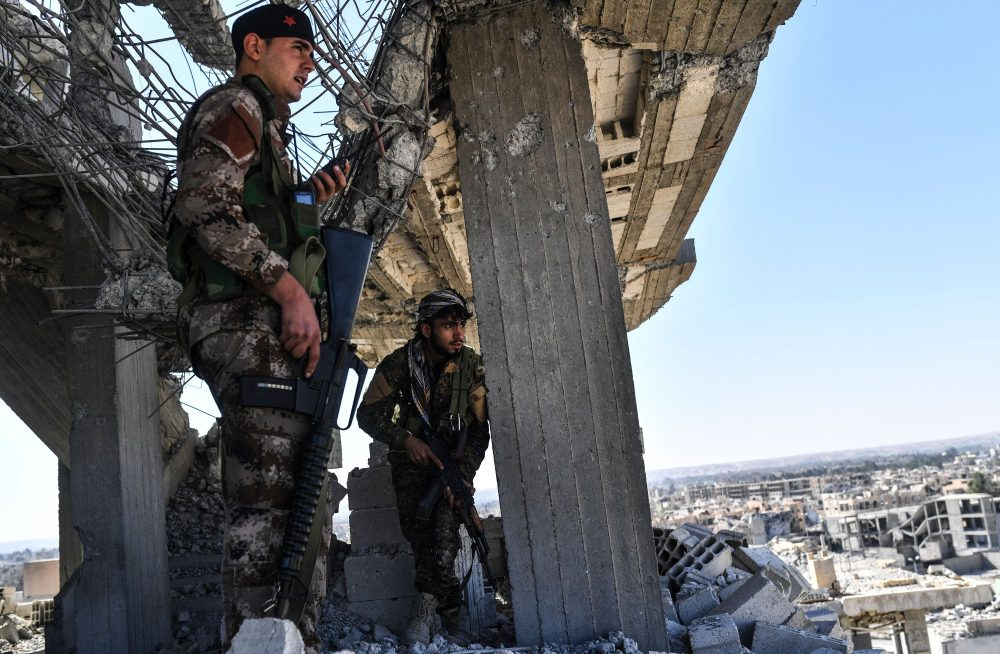 Members of the Syrian Democratic Forces (SDF), backed by U.S. special forces, walk on a building near Raqqa's central hospital as they clear the last positions on the frontline on Oct. 16, 2017, in the Islamic State group jihadists' crumbling stronghold. (Bulent Kilic/AFP/Getty Images)