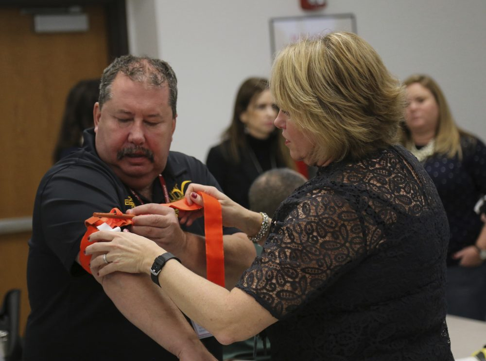 Two staffers from the Three Village Central School District in Stony Brook, N.Y., practice applying a tourniquet to one another during a first aid training session at Stony Brook University, Tuesday, Nov. 29, 2016, in New York. (Michael Balsamo/AP)