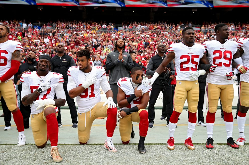 K'Waun Williams, Arik Armstead and Eli Harold of the San Francisco 49ers kneel while holding their hands over their chest during the U.S. national anthem before playing against the Washington Redskins at FedExField on Oct. 15, 2017, in Landover, Md. (Patrick Smith/Getty Images)
